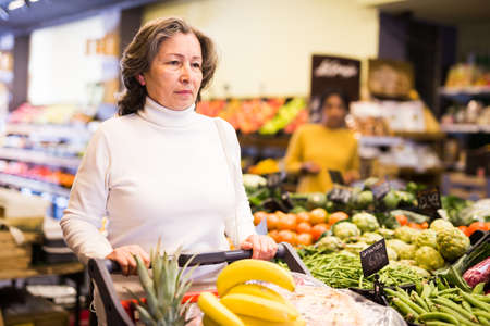 Casual woman doing shopping in grocery department of supermarket