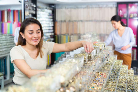 Positive woman chooses jewelry and other goods in jewelry store 免版税图像