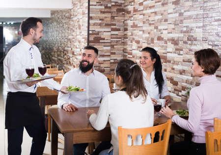 Waiter bringing order to visitors