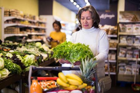 Female elderly shopper choosing ripe salad at supermarket 免版税图像