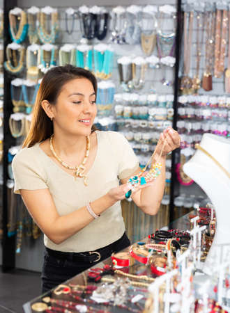 Young positive woman choosing necklace in shop 免版税图像