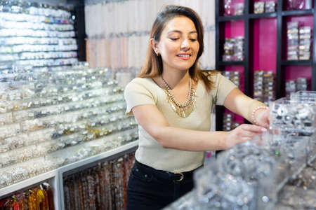 Young adult woman choosing bijouterie in store
