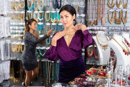 Asian woman looking for elegant necklace in bijouterie boutique 免版税图像