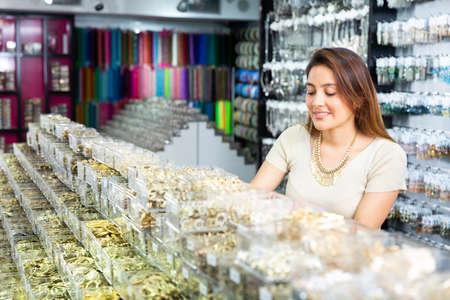 Hispanic woman choosing bijouterie in jewelry accessories store