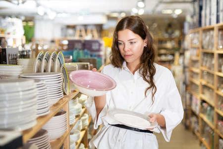 Woman chooses plates in tableware store Reklamní fotografie