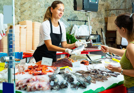 saleswoman offering fresh whole sea bass to buyer Banque d'images