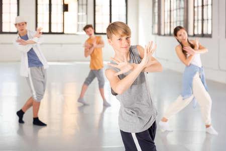 Group teenagers dancing hip-hop indoors