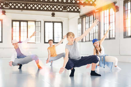 Team of young dancers training moves