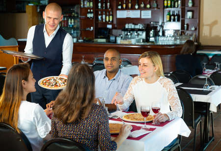 Smiling waiter serving pizza to group of people in restaurant Banque d'images
