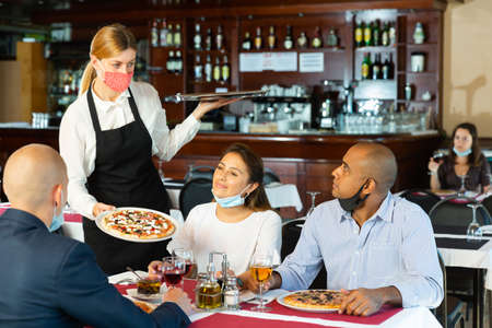 Polite waitress in protective mask bringing ordered pizza to friends visited restaurant Banque d'images