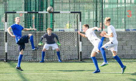 Youthful football players challenging for ball Stock fotó