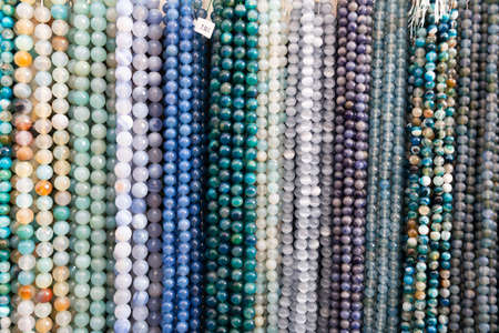 Beads from gems strung on thread in jewelry accessories store