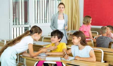 Concentrated preteen girls and boys solving teacher assignments in groups