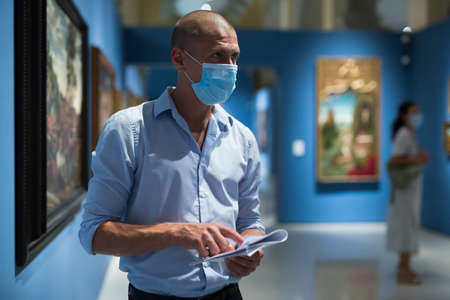 Portrait of man in face mask in gallery