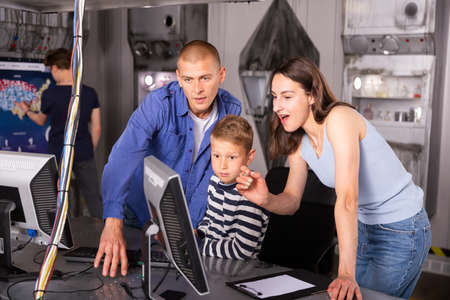Friendly family at a computer, thinking about solving a puzzle in a quest room Standard-Bild