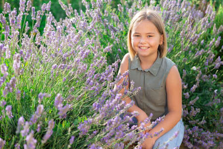 Little girl beside lavender shrub