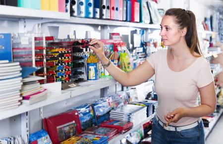 Woman choosing color pencil, color copybook Stockfoto