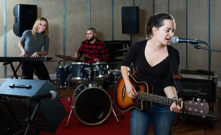 excited girl rock singer with guitar during rehearsal