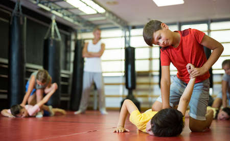 Boys and girls in gym exercising armlock move