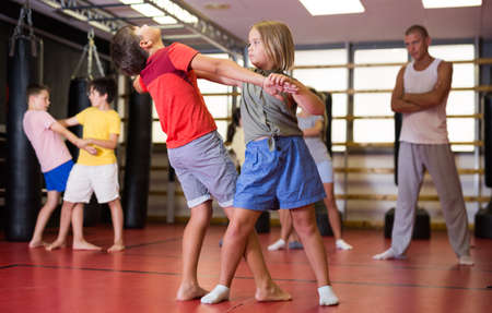 Girls and boys training self-protection moves on each other