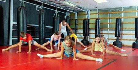 Kids doing leg-split in gym
