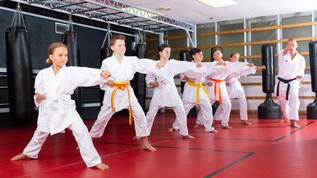 Group of girls and boys in kimono doing kata
