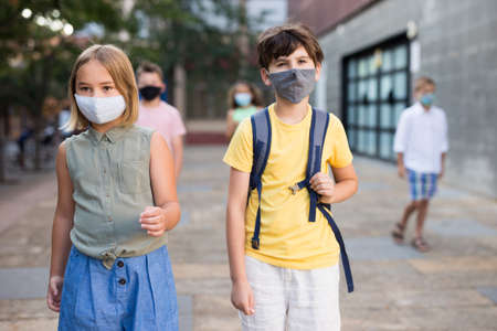 Young girl and boy in masks walking together