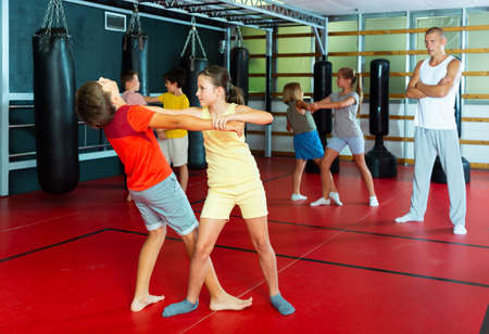 Girls and boys training self-protection moves on each other Stock fotó