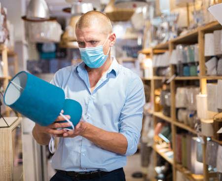 Man in face mask choosing table lamps in store Stock fotó