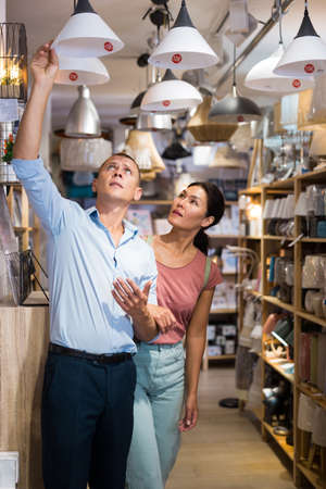 Man and woman choosing lamps in store