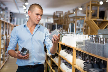 Man choosing toothbrush holder and soap dispencer Stock fotó