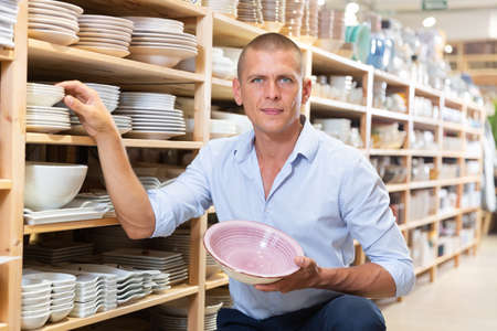 Man looking for new plate in store Stock fotó