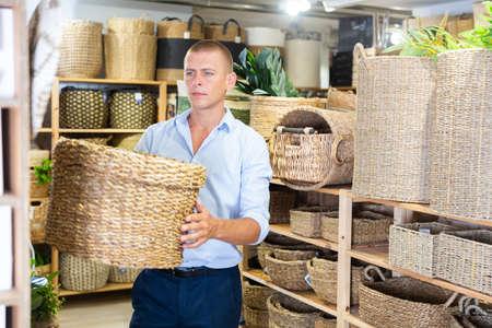 Man choosing wicker basket in store