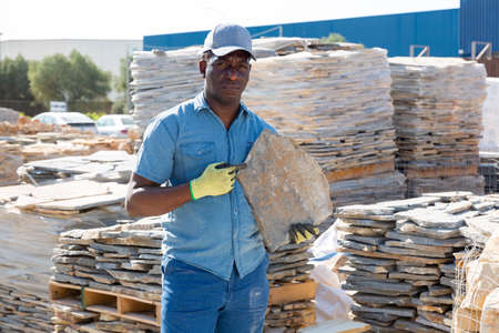 Man holding stone while standing in outdoor warehouse