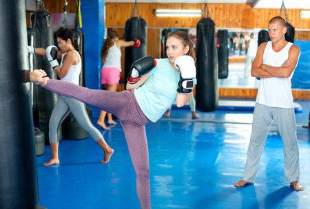 Woman kicking punchbag