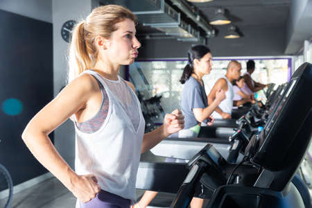 Focused woman training on treadmill in gy Stock fotó