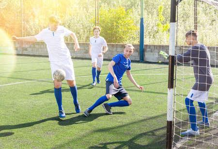 Junior football teams having golmouth scramble