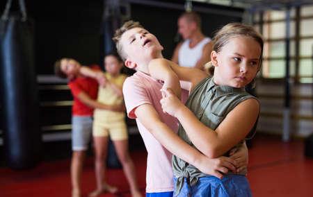 Girls and boys training chin strike in gym