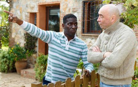 Disgruntled men talking in backyard