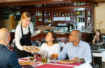 Young waitress serving ordered pizza to guests in restaurant Banque d'images
