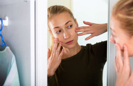 Cheerful woman is concentrared looking on her face in the mirror at the home