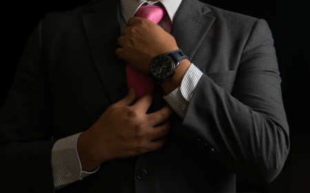 Successful businessman on black background, smoking and tie