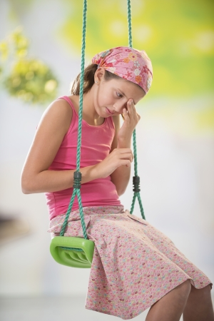 10 12 years: sad girl on a swing in the garden