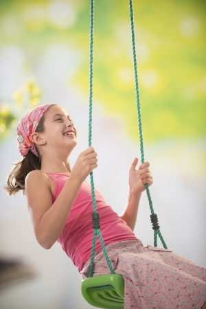 10 to 12 years: young girl on a swing in the garden