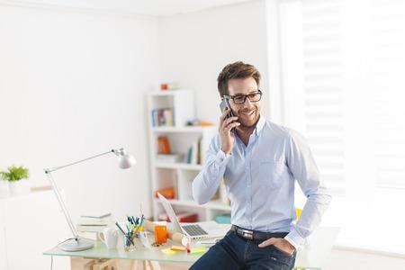 malé: Mladý muž na telefonu v kanceláři