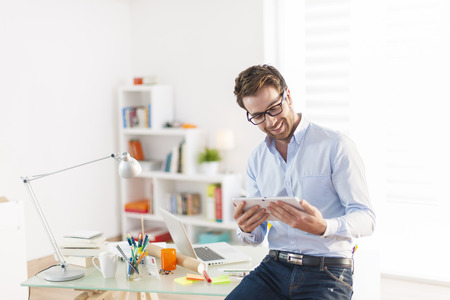 view of an elegant office: young man using a digital tablet at office