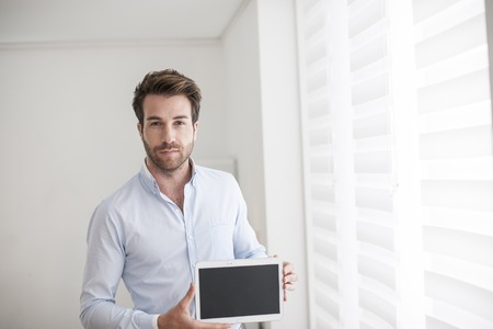 man front view: young man using a digital tablet Stock Photo