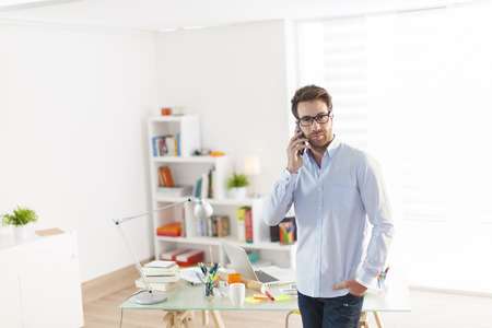 front desk: young man at phone standing in front his desk Stock Photo