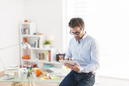 ejecutivos: hombre joven que usa una tableta digital en la oficina Foto de archivo