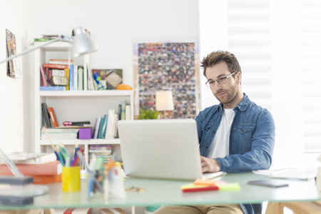 jonge man werkt op een laptop binnenshuis Stockfoto